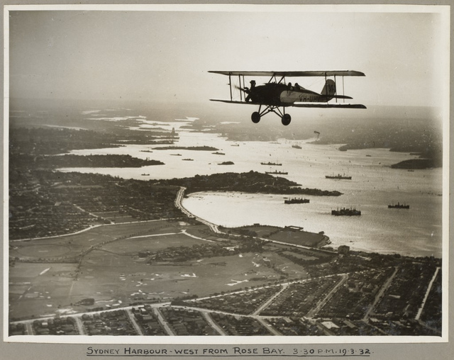 American Eagle model A-1 biplane VH-UHV in flight above Sydney Harbour, 19 March 1932