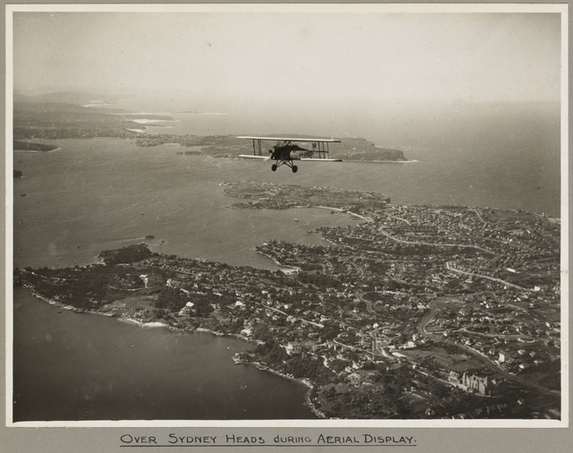 American Eagle model A-1 biplane VH-UHV in flight above Sydney Heads, 19 March 1932