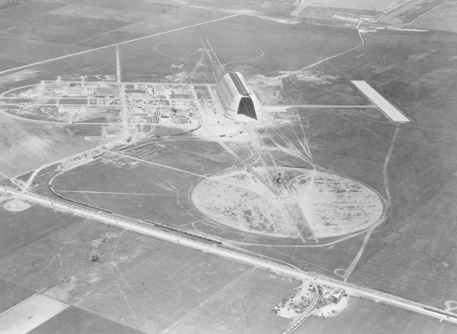 NAS Sunnyvale Station, Mt. View CA Looking North  (Moffett Field) at the top of the image the Kingsport Plunge and the dock can be seen.  Thought the plunge closed in the late 20's  the structure is still standing. ARC-1933-A93-0073-3