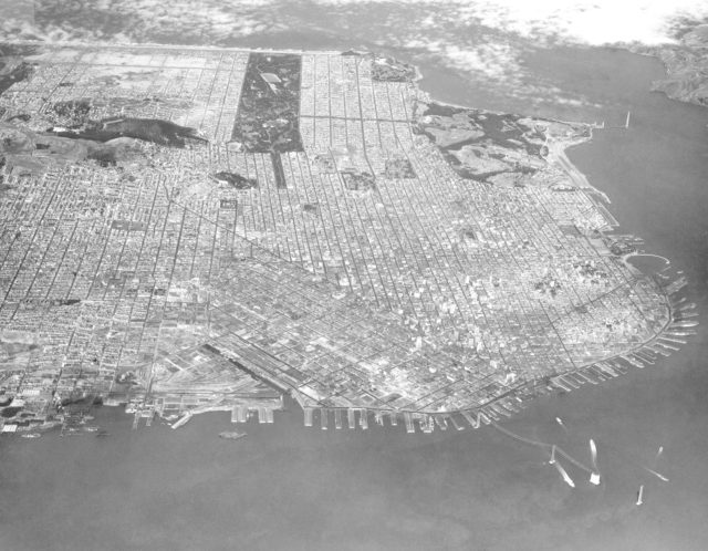 Navy Aerial of San Francisco, California; looking west across South Beach - China Basin to Golden Gate Park, includes Richmond District, Sea Cliff, Presidio, Marina, Fisherman's Wharf,  and Telegraph Hill. - Note the beginings of the Golden Gate Bridge in the upper right and the Bay Bridge construction in the lower right of the image. ARC-1935-A93-0075-2
