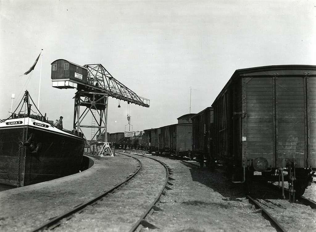 """HUA-163263-Afbeelding van goederenwagens van de N.S. op de kade van de haven te Nijmegen, met links het schip """"Emma"""""""