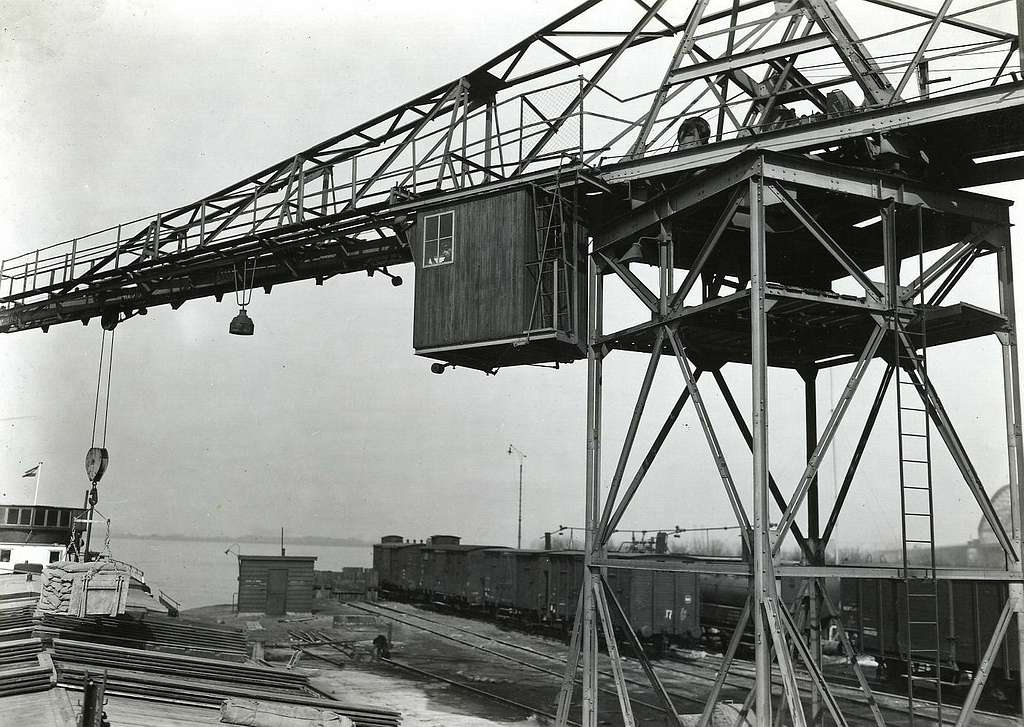 HUA-163264-Afbeelding van de kraan voor overslag van goederen van trein op schip in de haven van Nijmegen. Op de achtergrond enkele opstelsporen met goederenwagens van de N.S