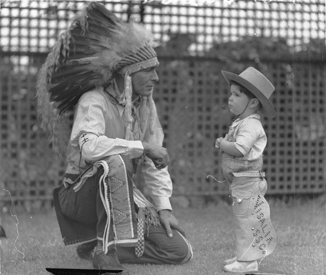 Visiting Indian Chief High Eagle talks with Johnny Schneider (aged about 3 or 4 and dressed in cowboy outfit), White City, Sydney, 11 Jan 1935 / photographer Sam Hood