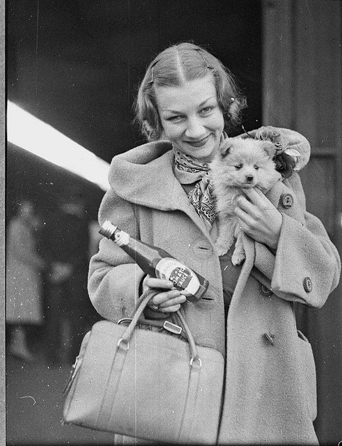 Ballet star Helene Kirsova with puppy and tomato sauce bottle on arrival back in Sydney for a return season, Central Railway Station, May 1937 / Sam Hood