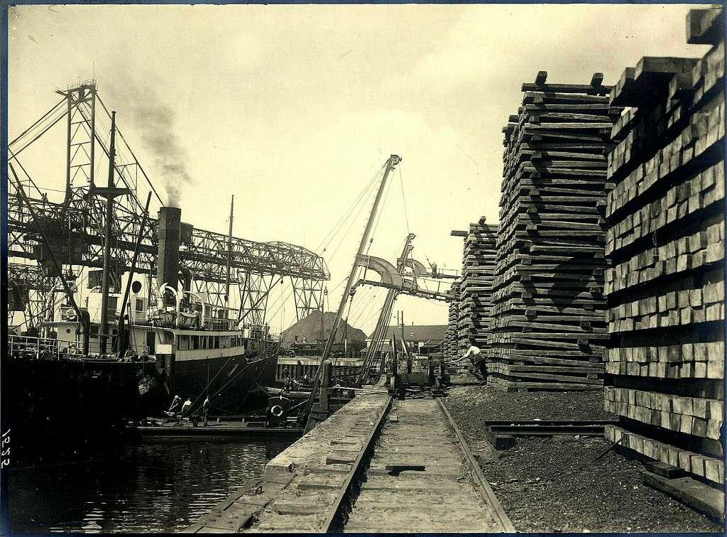 HUA-163311-Afbeelding van het lossen van nog onbehandelde dwarsliggers voor de N.S. in de haven van Dordrecht