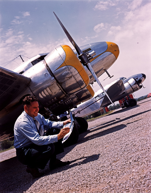 [Man in front of Lockheed 12A Electra Junior Airplanes]
