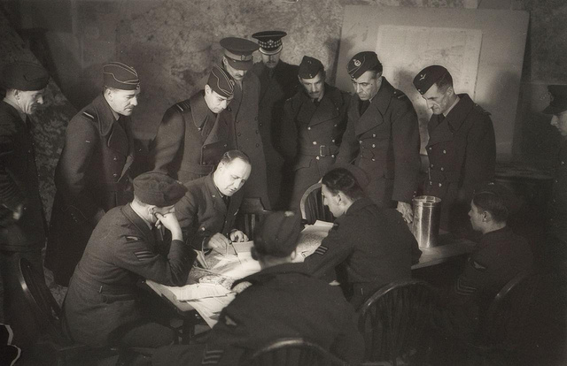 Senior RAF and army officers and King George VI - debrief from a bombing raid with the crew of a Wellington