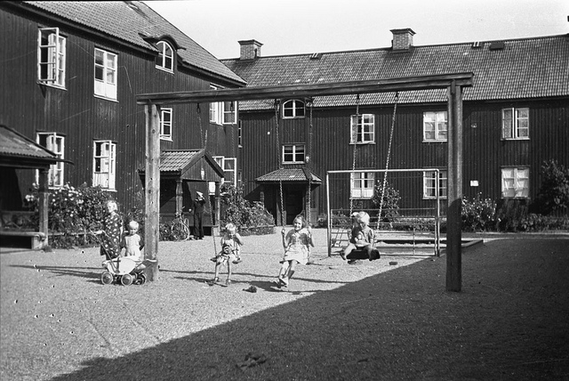 Children on a swing in front of house in Stockholm 1942
