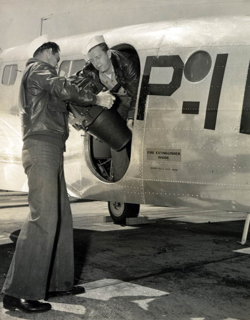 Naval Photography School students loading aerial camera on to a plane at NAS Pensacola