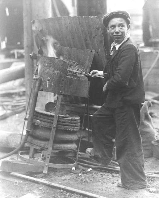An apprentice heating rivets at J.L. Thompson & Sons Ltd