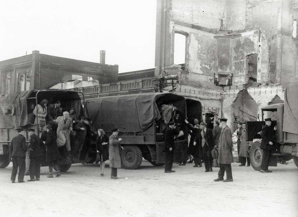 HUA-168056-Afbeelding van vrachtauto's van het Canadese leger die ingezet worden door de N.S. als vervangend vervoer voor treintreizigers op het Stationsplein te Arnhem. Op de achtergrond het tijdens de oorlog v