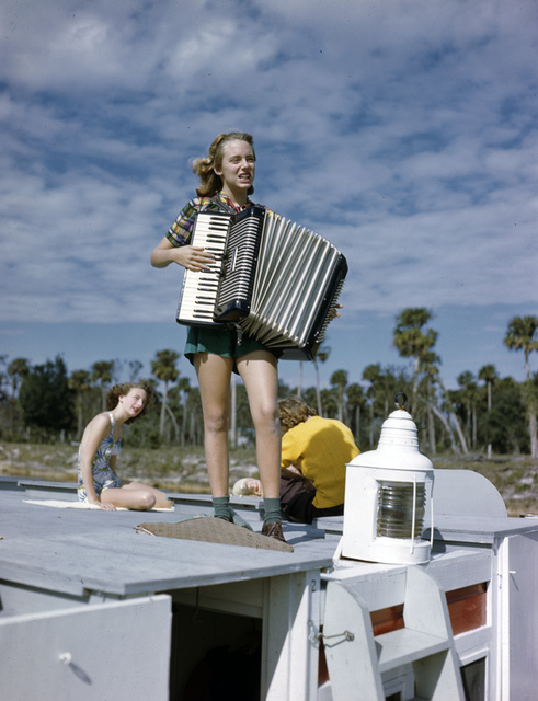 Lois Duncan Steinmetz playing the accordian aboard the shantyboat Lazy Bones