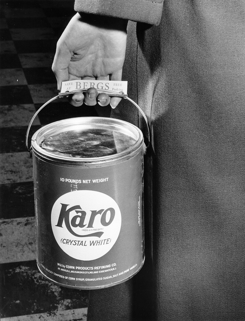 A person carrying a can of Karo syrup at Berg's Supermarket, circa 1950