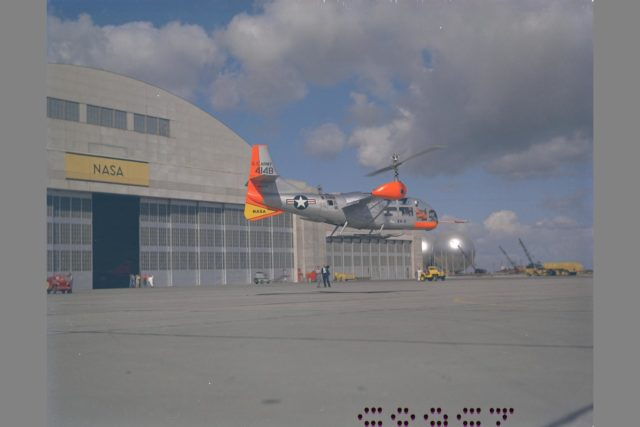 XV-3 HOVERING ON RAMP.  Flight Test of Bell XV-3 Convertiplane.  Bell VTOL tilt-rotor aircraft hovering in front of building N-211 at Moffett Field. The XV-3 design combined a helicopter rotor and a wing. A 450 horsepower Pratt & Whitney piston engine drove the two rotors. The XV-3, first flown in 1955 , was the first tilt-rotor to achieve 100% tilting of rotors. The vehicle was underpowered, however, and could not hover out of ground effect. Note the large ventral fin, which was added to imrpove directional stability in cruse (Oct 1962) ARC-1959-AC-25685