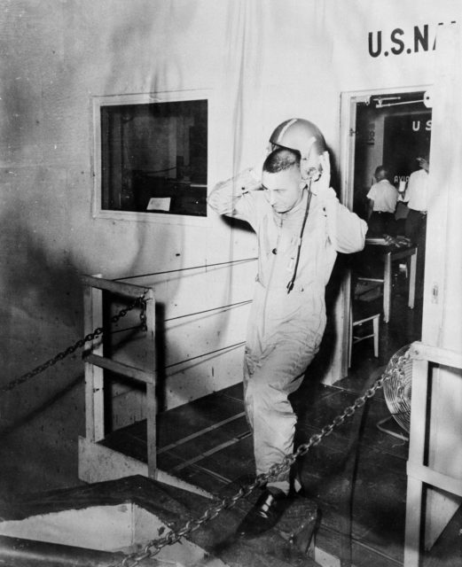 B59-00587 (1959) --- Astronaut Virgil (Gus) Grissom is pictured leaving a U.S. Navy installation and removing his helmet. Photo credit: NASA b59-00587
