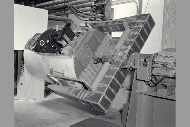 3/4 rear view with pilot Merriweather - 60 degrees bank angle. NE-2 degree of freedom simulator set-up for pitch and roll motion. ARC-1960-A-26446