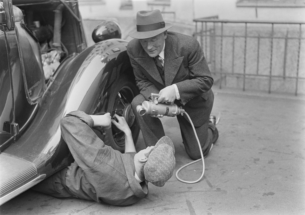 Radio reporter Alexis af Enehjelm interviewing a man fixing a car, 1930s.