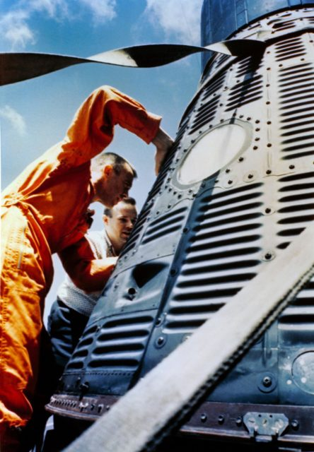 Astronaut Alan Shepard inspects his capsule on U.S. Champlain after recovery