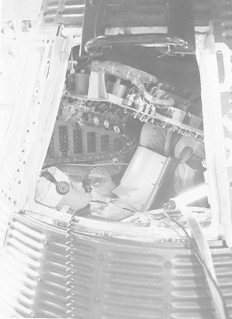 Astronaut John Glenn inspecting interior of Mercury capsule