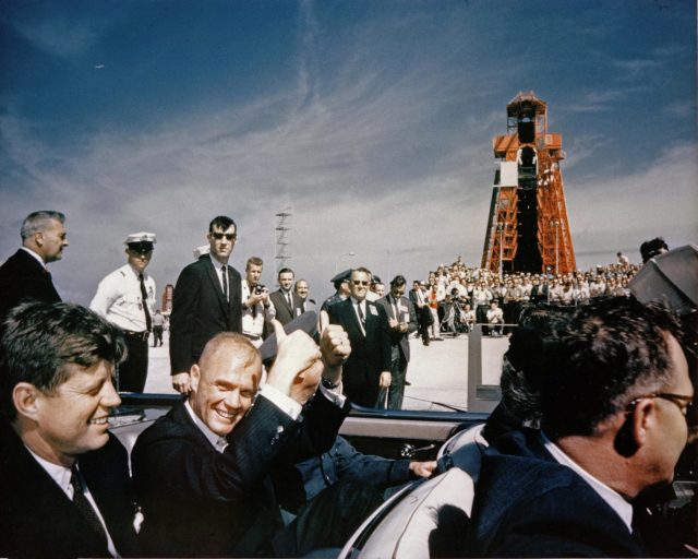 CAPE CANAVERAL Fla. -- Astronaut John H. Glenn Jr. gives a double thumbs-up as he and President John F. Kennedy arrive at the Cape Canaveral Missile Test Annex in Florida. Glenn's Mercury Atlas 6 mission lifted off from Launch Complex 14, in the background, on Feb. 20, 1962. Photo Credit: NASA KSC-62C-0363