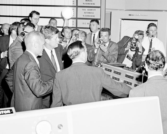CAPE CANAVERAL Fla. -- Photojournalists crowd in as astronaut John H. Glenn Jr., left, talks to President John F. Kennedy about a console in the Mercury Control Center at the Cape Canaveral Missile Test Annex in Florida. Photo Credit: NASA KSC-PL62-76876