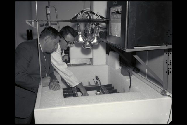 Dr H. 'Chuck' Klein (l) with Dr R. Young  looking into the Mars box (simulator), which simulated the environment of Mars for the preparation of life sciences experiments for the Viking lander. ARC-1963-A-31494