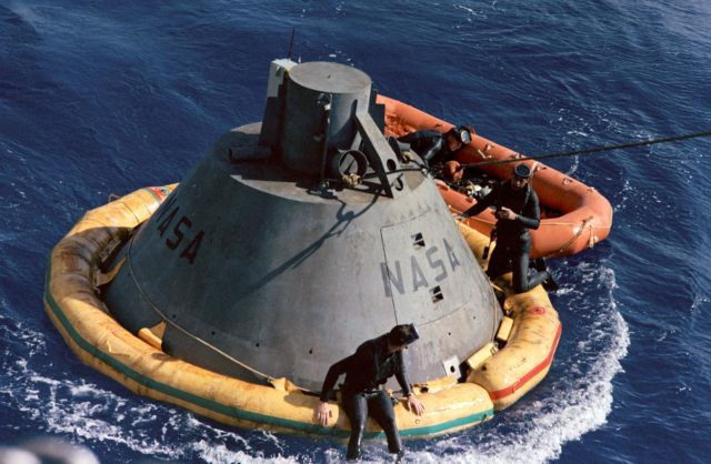 Frogmen on Apollo command module boilerplate flotation collar during recovery