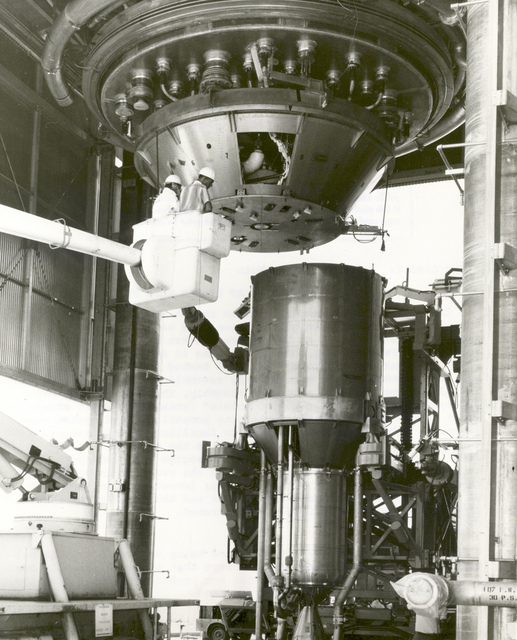 """The first ground experimental nuclear rocket engine (XE) assembly, in a """"cold flow"""" configuration, is shown being installed in Engine Test Stand No. 1 at the Nuclear Rocket Development Station in Jackass Flats, Nevada. Cold flow experiments are conducted"""