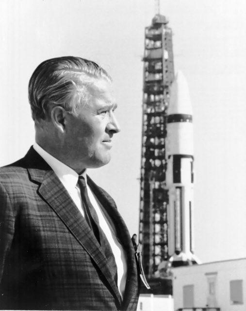 Wernher von Braun stands in front of a Saturn IB