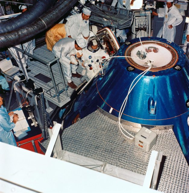 Astronaut John Young ingresses Apollo spacecraft command module in training