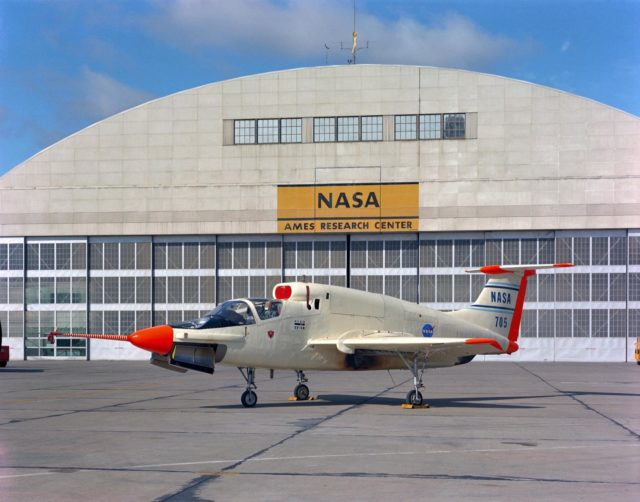 XV-5B (NASA-705) on Flight Line at Ames Research Center with hangar in the background. ARC-1969-AC-41358
