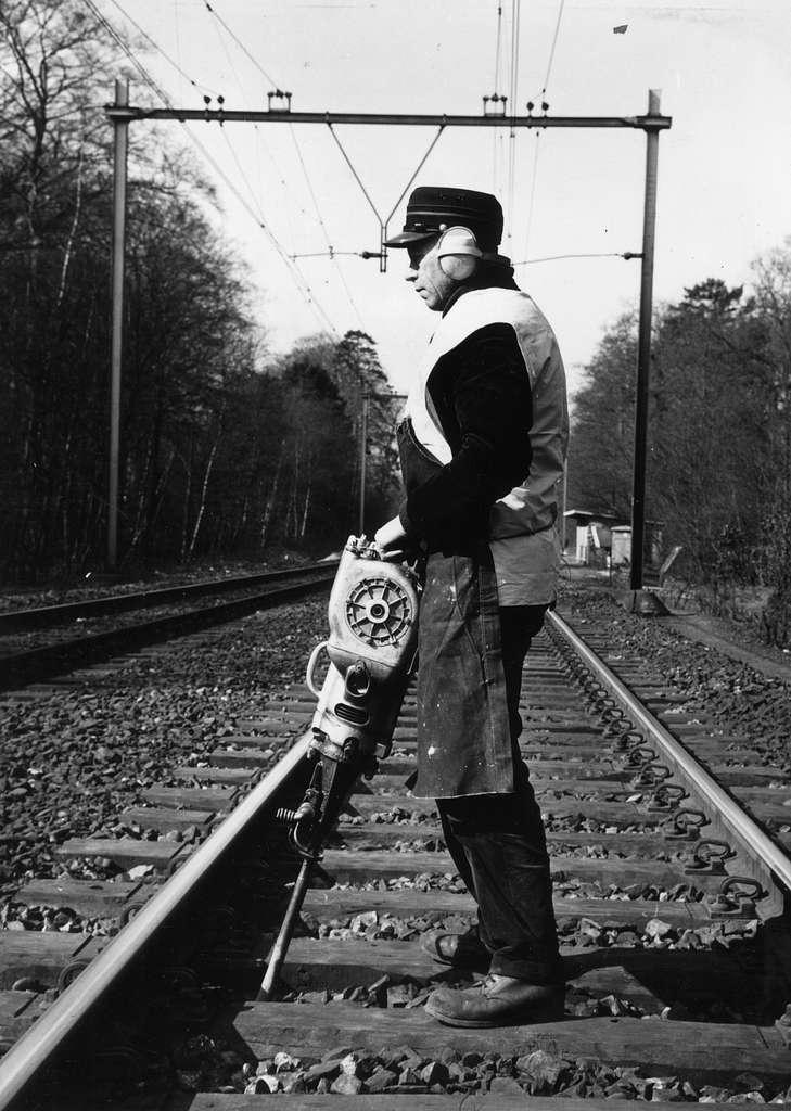 HUA-169033-Afbeelding van een wegwerker van de N.S. met een trilstand tijdens onderhoudswerkzaamheden aan de spoorlijn nabij Driebergen-Zeist