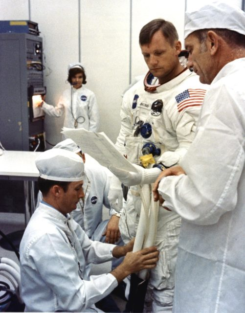 Apollo 11 Commander Neil Armstrong is looking over flight plans while being assisted by a spacesuit technician during suiting operations in the Manned Spacecraft Operations Building (MSOB) prior to the astronauts' departure to Launch Pad 39A. The three astronauts, Edwin E. Aldrin Jr., Neil A. Armstrong and Michael Collins will then board the Saturn V launch vehicle, scheduled for a 9:32 a.m. EDT liftoff, for the first manned lunar landing mission ksc-69pc-376