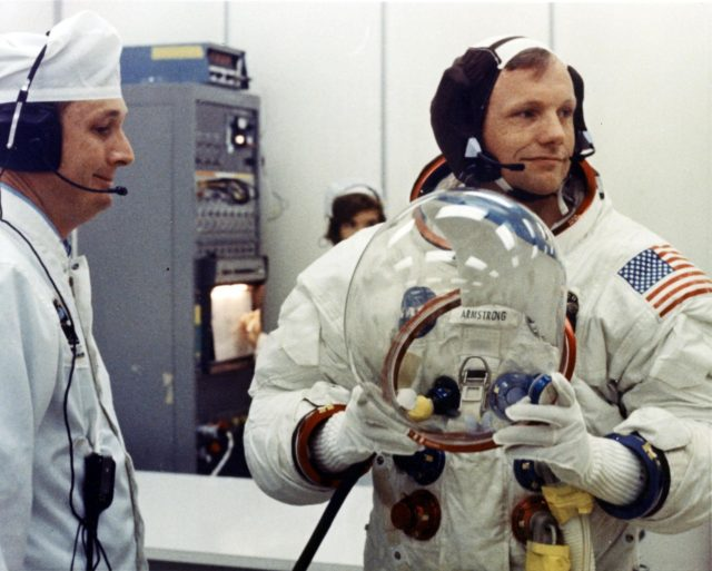 Apollo 11 Commander Neil Armstrong prepares to put on his helmet with the assistance of a spacesuit technician during suiting operations in the Manned Spacecraft Operations Building (MSOB) prior to the astronauts' departure to Launch Pad 39A. The three astronauts, Edwin E. Aldrin Jr., Neil A Armstrong and Michael Collins, will then board the Saturn V launch vehicle, scheduled for a 9:32 a.m. EDT liftoff, for the first manned lunar landing mission ksc-69pc-377