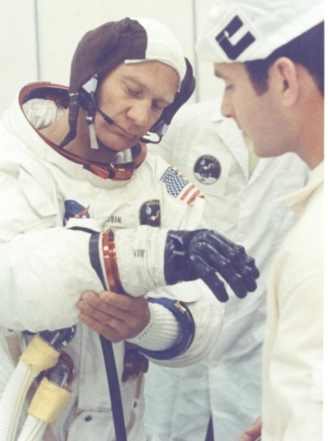 KENNEDY SPACE CENTER, FLA. - Apollo 11 astronaut Edwin E. Aldrin Jr. is being assisted by a spacesuit technician during suiting operations in the Manned Spacecraft Operations Building prior to the astronauts' departure to Launch Pad 39A.  The three astronauts, Edwin E. Aldrin Jr., Neil A Armstrong and Michael Collins, will then board the Saturn V launch vehicle, scheduled for a 9:32 a.m. EDT liftoff for the first manned lunar landing mission. KSC-69PC-381