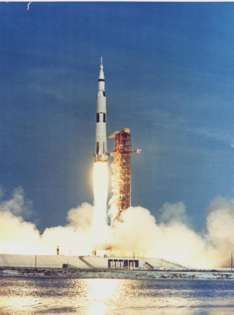 KENNEDY SPACE CENTER, FLA. - The Apollo 11 Saturn V space vehicle rises past the launch tower as it lifts off with astronauts Neil A. Armstrong, Michael Collins and Edwin E. Aldrin Jr. at 9:32 a.m. EDT July 16, 1969, from KSC's Launch Complex 39A.  During the planned eight-day mission, Armstrong and Aldrin will descend in a Lunar Module (LM) to the Moon's surface while Collins orbits overhead in the Command Module. The two astronauts are to spend 22 hours on the Moon, including two-and-one-half hours outside the LM. They will gather samples of lunar material and will deploy scientific experiments that will transmit data about the lunar environment.  They will rejoin Collins in the Command Module for the return trip to Earth. KSC-69PC-391
