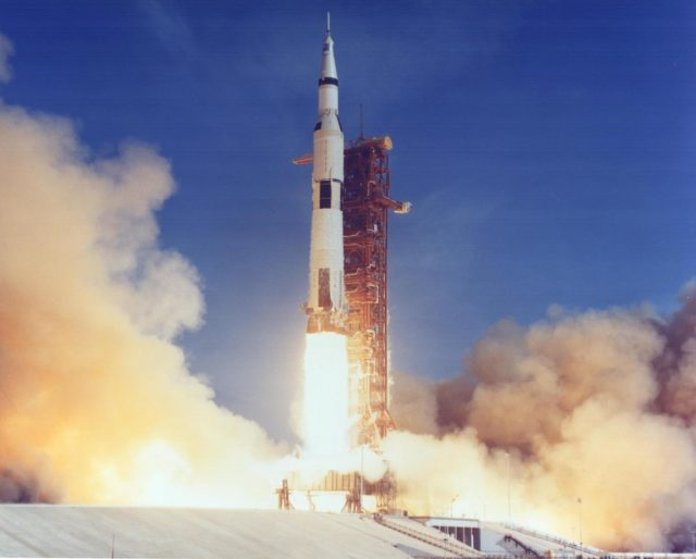 KENNEDY SPACE CENTER, FLA. - The Apollo 11 Saturn V space vehicle lifted off with astronauts Neil A. Armstrong, Michael Collins and Edwin E. Aldrin Jr. at 9:32 a.m. EDT July 16, 1969, from KSC's Launch Complex 39A.  During the planned eight-day mission, Armstrong and Aldrin will descend in a Lunar Module (LM) to the Moon's surface while Collins orbits overhead in the Command Module. The two astronauts are to spend 22 hours on the Moon, including two-and-one-half hours outside the LM. They will gather samples of lunar material and will deploy scientific experiments that will transmit data about the lunar environment.  They will rejoin Collins in the Command Module for the return trip to Earth. KSC-69PC-393