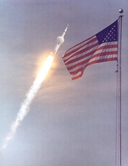 KENNEDY SPACE CENTER, FLA. - The American flag heralds the flight of Apollo 11, man's first lunar landing mission.  The Apollo 11 Saturn V space vehicle lifted off with astronauts Neil A. Armstrong, Michael Collins and Edwin E. Aldrin Jr. at 9:32 a.m. EDT from KSC's Launch Complex 39A.  During the planned eight-day mission, Armstrong and Aldrin will descend in a Lunar Module (LM) to the Moon's surface while Collins orbits overhead in the Command Module. The two astronauts are to spend 22 hours on the Moon, including two-and-one-half hours outside the LM. They will gather samples of lunar material and will deploy scientific experiments that will transmit data about the lunar environment.  They will rejoin Collins in the Command Module for the return trip to Earth. KSC-69PC-397