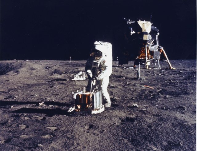 JOHNSON SPACE CENTER, HOUSTON, TEXAS  - The deployment of the early Apollo scientific experiments package is photographed by astronaut Neil A. Armstrong during the Apollo 11 EVA.  Here, astronaut Aldrin is deploying the passive seismic experiments package (PSEP).  Already deployed is the Laser Ranging Retro-Reflector (LR-3), which can be seen to the left and farther in the background.  In the center background is the Lunar Module (LM). A flag of the United States is deployed near the LM.  In the far left background is the deployed black and white lunar surface television camera.  Armstrong took this picture with the 70-mm ALSC. KSC-as11-40-5946