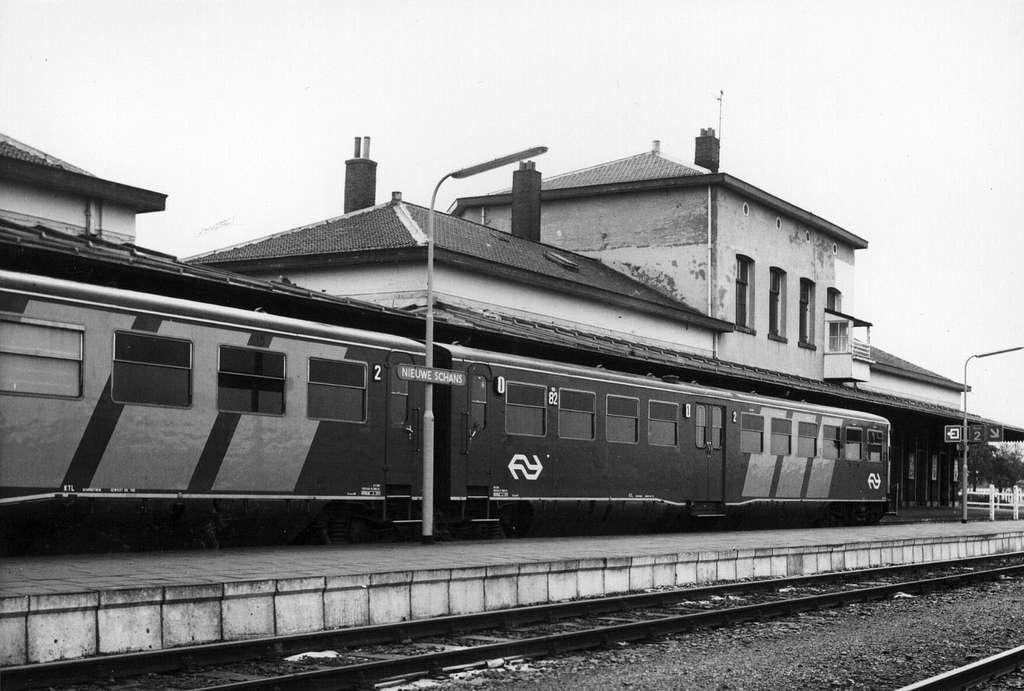 HUA-154997-Gezicht op de perronzijde van het NS station Nieuweschans te Nieuweschans met langs het perron het diesel electrische treinstel nr 82 DE 2 Blauwe Enge