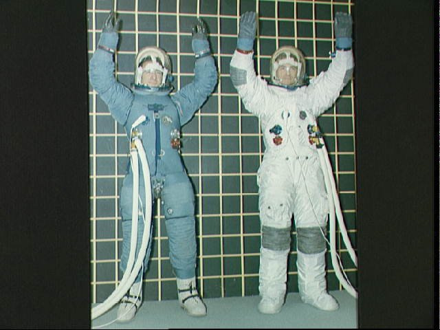 Two astronauts check mobility of different types of Apollo space suits