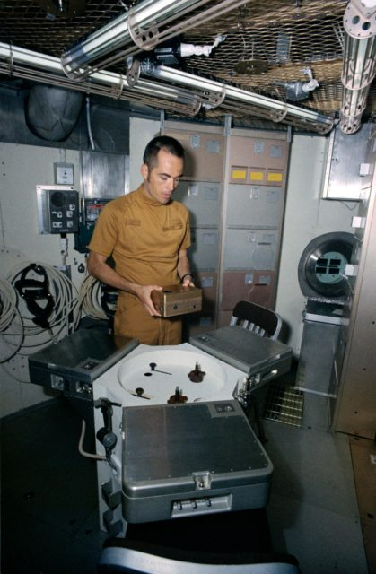 Astronaut Robert Crippen holds training model of Skylab experiment