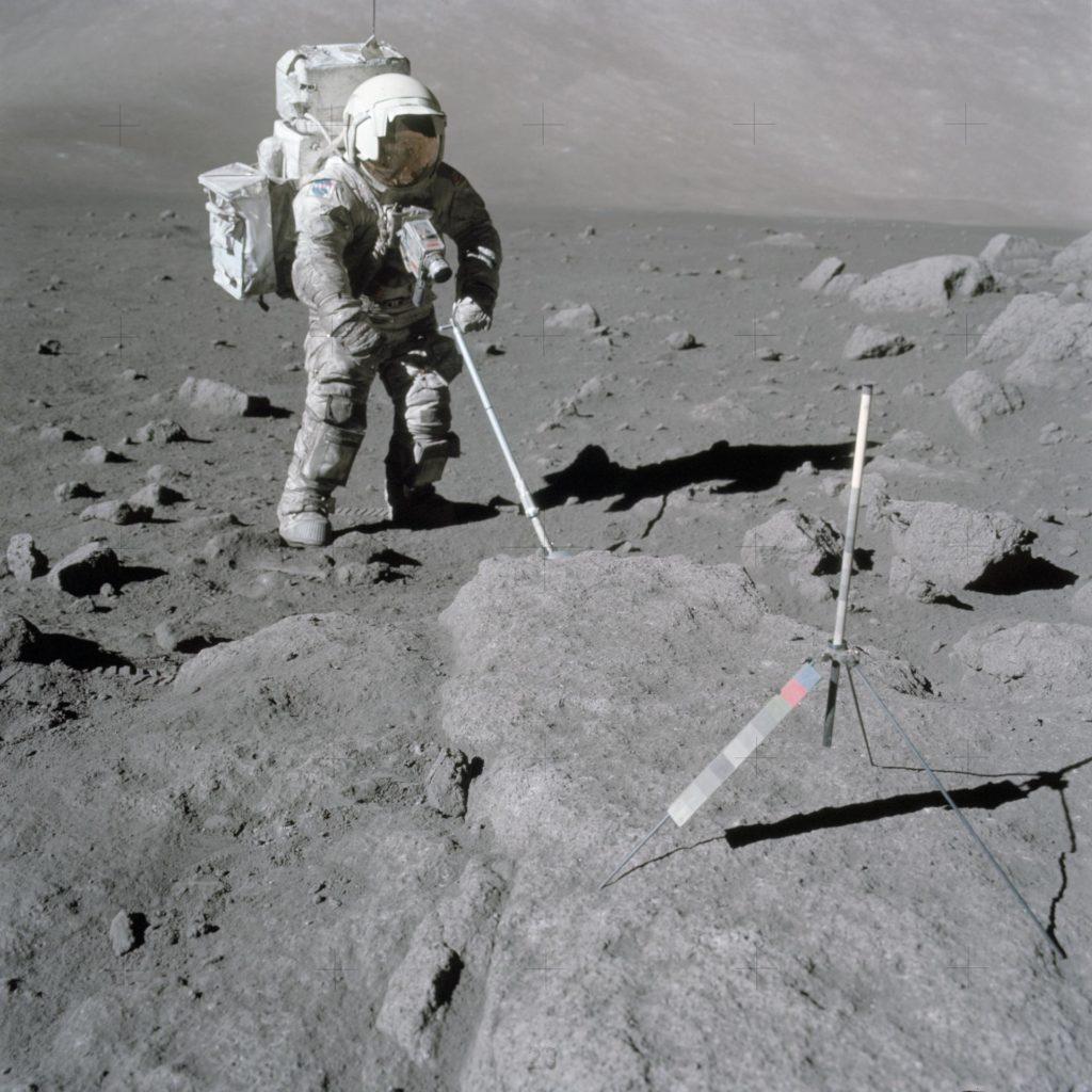 Astronaut Harrison Schmitt uses scoop to retrieve lunar samples during EVA