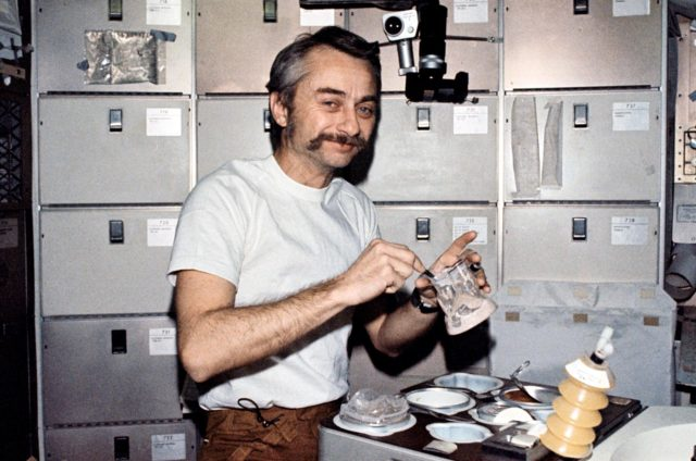 SL3-111-1519 (6 Aug. 1973) --- Scientist-astronaut Owen K. Garriott, Skylab 3 science pilot, reconstitutes a pre-packaged container of food at the crew quarters ward room table of the Orbital Workshop (OWS) of the Skylab Space Station cluster. This picture was taken with a hand-held 35mm Nikon camera.  Astronauts Garriott, Alan L. Bean and Jack R. Lousma remained with the Skylab Space Station in Earth orbit for a total of 59 days conducting numerous medical, scientific and technological experiments. Note the knife and fork on the food tray and the utensil with which Garriott stirs the food mixed with water. Skylab is the first manned space program by NASA which affords the crew men an opportunity to eat with the same type utensils used on Earth. Photo credit: NASA SL3-111-01519