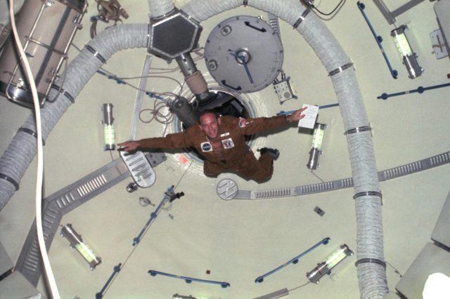 Astronaut Jack Lousma doing acrobatics in OWS dome area