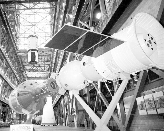 CAPE CANAVERAL, Fla. – Model of docked Apollo and Soyuz spacecraft in the foreground and skylight in the Vehicle Assembly Building high bay frame the second stage of the Saturn 1B booster that will launch the United States ASTP mission as a crane raises it prior to its mating with the Saturn 1B first stage.  Mating of the Saturn 1B first and second stages was completed this morning.  The U. S. ASTP launch with mission commander Thomas Stafford, command module pilot Vance Brand and docking module pilot Donald Slayton is scheduled at 3:50 p.m. EDT July 15.      The first international crewed spaceflight was a joint U.S.-U.S.S.R. rendezvous and docking mission.  The Apollo-Soyuz Test Project, or ASTP, took its name from the spacecraft employed: the American Apollo and the Soviet Soyuz.  The three-man Apollo crew lifted off from Kennedy Space Center aboard a Saturn IB rocket on July 15, 1975, to link up with the Soyuz that had launched a few hours earlier.  A cylindrical docking module served as an airlock between the two spacecraft for transfer of the crew members.  Photo credit: NASA KSC-108-75P-0005