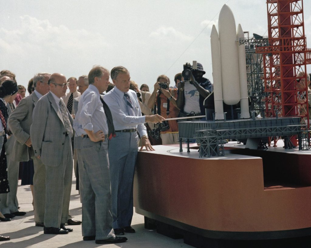 CAPE CANAVERAL, Fla. -- At the Kennedy Space Center in Florida, President Jimmy Carter, hand on waist, is briefed on preparations for the first space shuttle launch by center director Lee Scherer. To the left of Carter is NASA Administrator Robert Frosch. Photo Credit: NASA KSC-78PC-0475