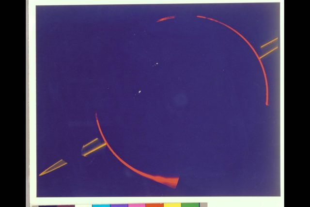 JUPITER'S FAINT RING SYSTEM IS SHOWN HERE AS TWO ORANGE LINES PROTRUDE FROM THE LEFT TOWARD JUPITER'S LIMB.  THIS COLORFUL COMPOSITE WAS TAKEN IN JUPITER'S SHADOW THROUGH ORANGE AND VIOLET FILTERS. THE COLORFUL IMAGES OF JUPITER'S LIMB ARE EVIDENCE OF THE SPACECRAFT MOTION DERING THIS LONG EXPOSURE.  VOYAGER 2 ARC-1979-AC79-7118