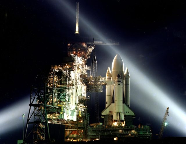 A timed exposure of the first Space Shuttle, STS-1, at Launch Pad A, Complex 39, turns the space vehicle and support facilities into a night-time fantasy of light. To the left of the Shuttle are the fixed and the rotating service structures. KSC-81PC-0136