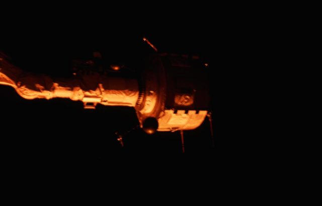 PDP grappled by RMS is positioned above payload bay (PLB) at sunrise